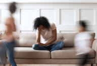 depressed young woman sitting on the couch