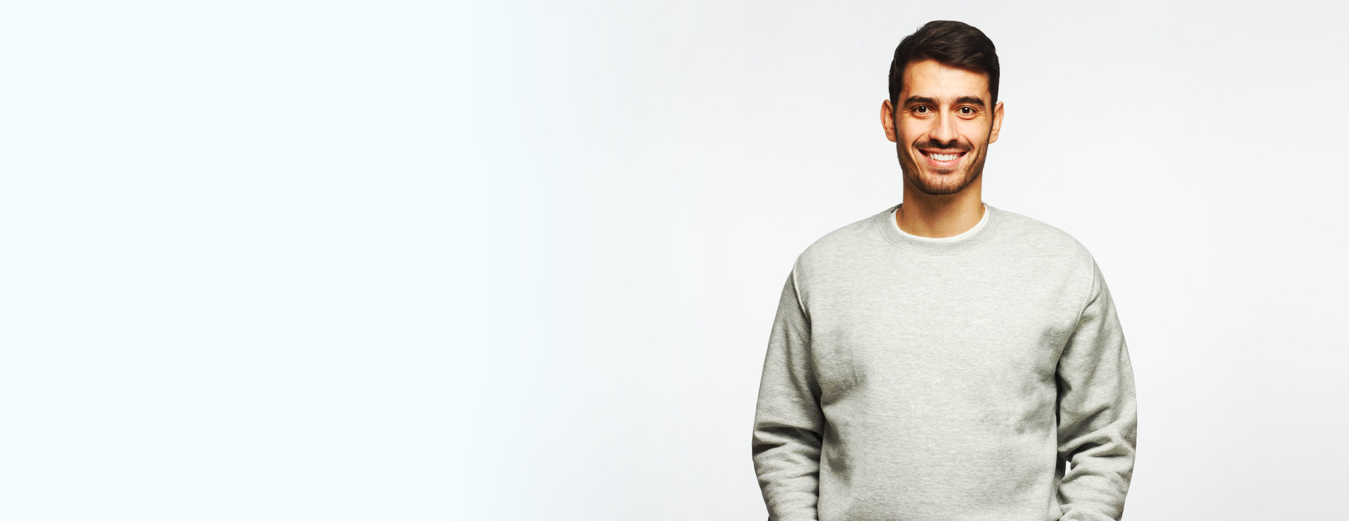 young man smiling and wearing gray longsleeve