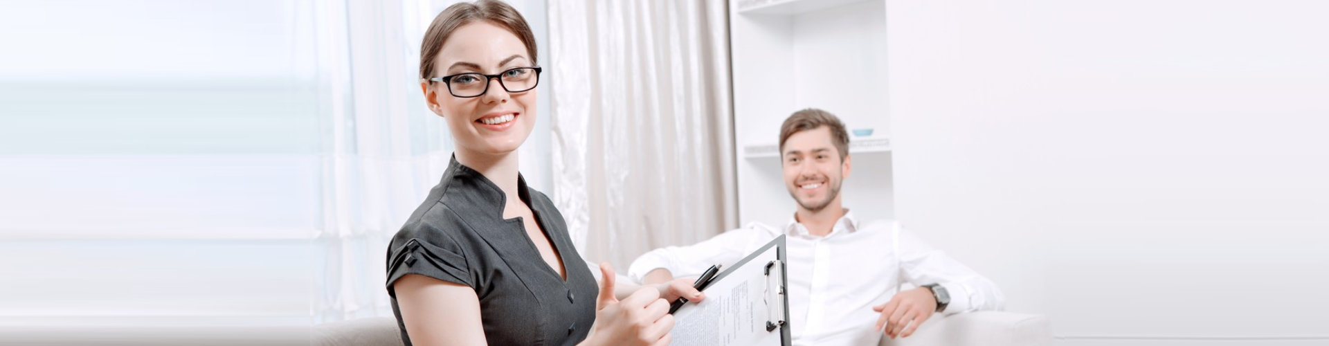 smiling male patient and beautiful female psychologist wearing eye glasses while holding documents
